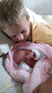 Baby Hannah in pink blanket with older brother