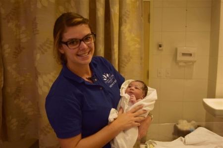 Student midwife interning at JoySpring from Mount Royal University holding baby Kezia