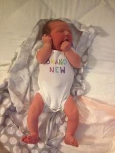 Newborn baby Mauve wearing Brand New onesie