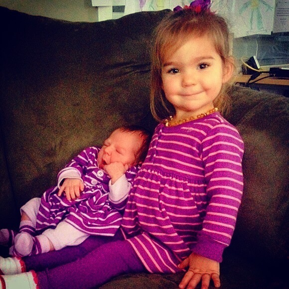 Baby Mauve and older sister wearing matching purple outfits