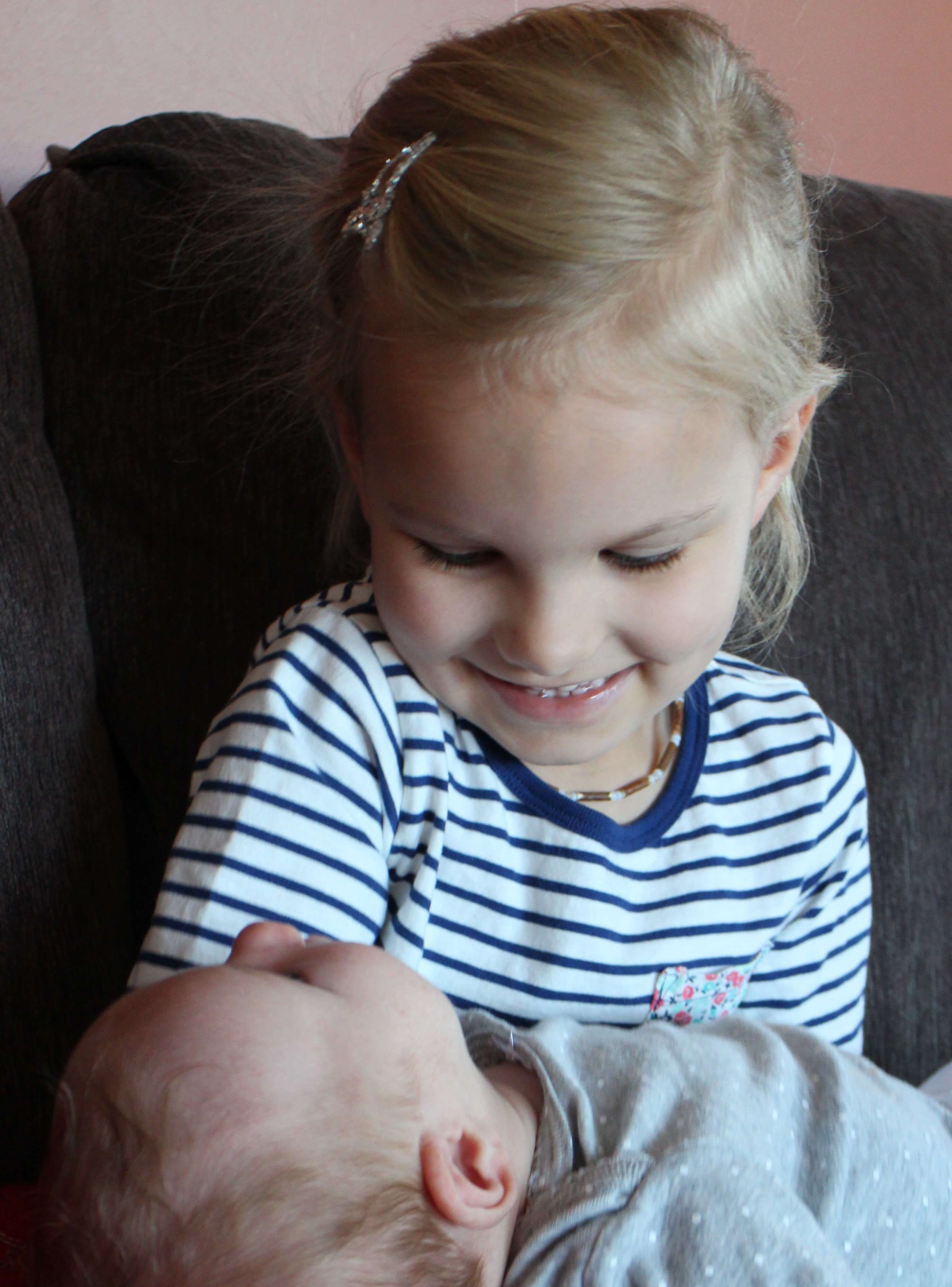 Jane cradling her little brother, recently born at JoySpring Midwifery
