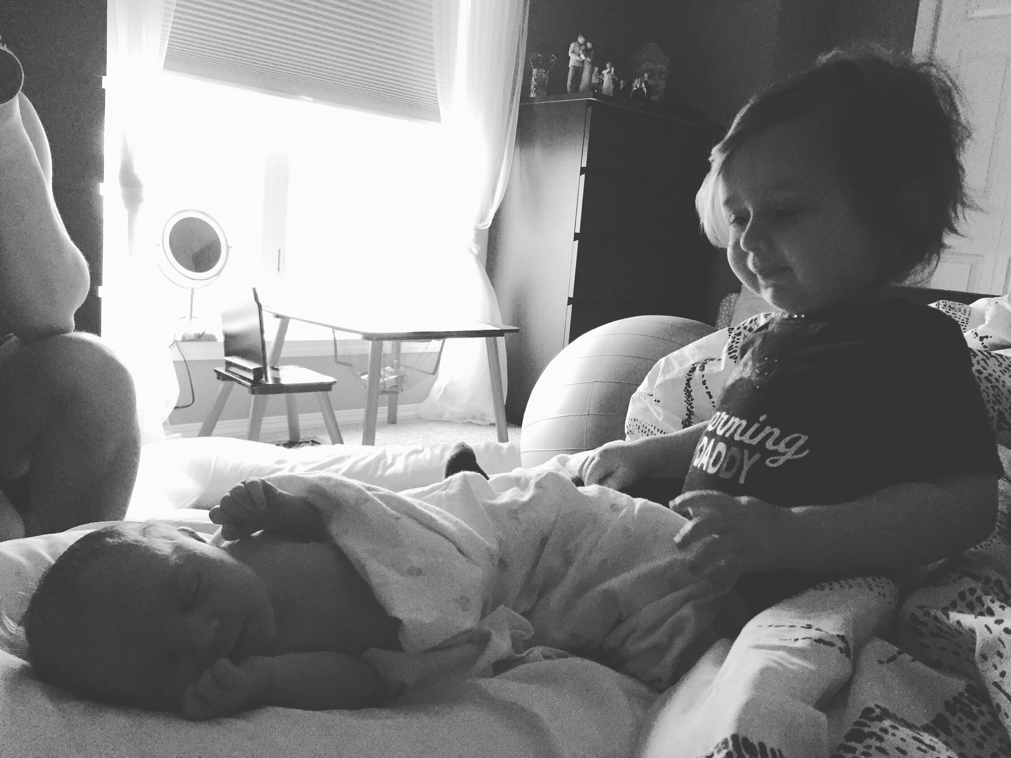 Older sister watching over newborn baby Luna