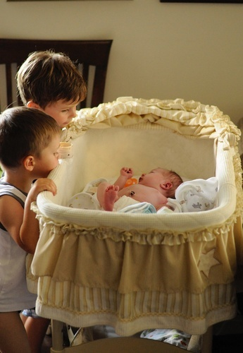 Newborn baby in crib with older brothers